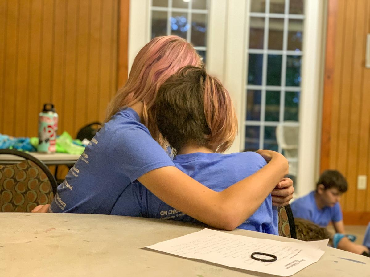 Two 12-year-olds comfort each other while sharing stories about their families. Some say it's only at camp that they don't feel alone because they meet other children in their situation. Some children have seen their parents overdose and some have had to