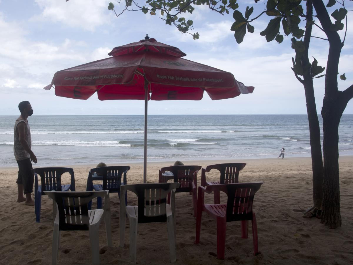 A beach vendor sets chairs as he waits for customers in Kuta beach in Bali, Indonesia, on Thursday. The Indonesian resort island of Bali welcomed international travelers to its shops and white-sand beaches for the first time in more than a year Thursday -