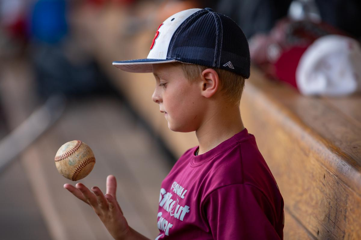 Fans of all ages including this young boy, the son of a player for the amateur team known as the Red Sox, turned out to watch his father's team play.