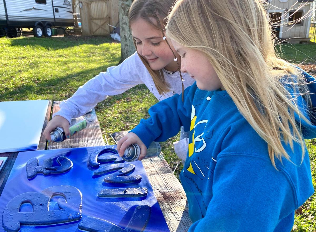 """Sisters, Raegan and Rylyn Richins look closely at one of their newly painted """"Be Kind"""" signs."""