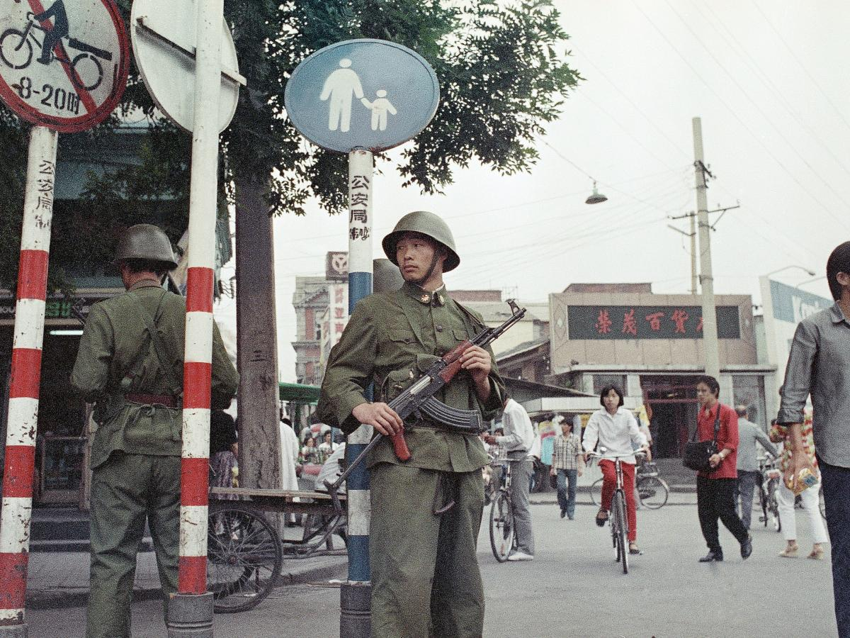 People's Liberation Army soldiers stand guard in a busy shopping district near Tiananmen Square on June 12, 1989.