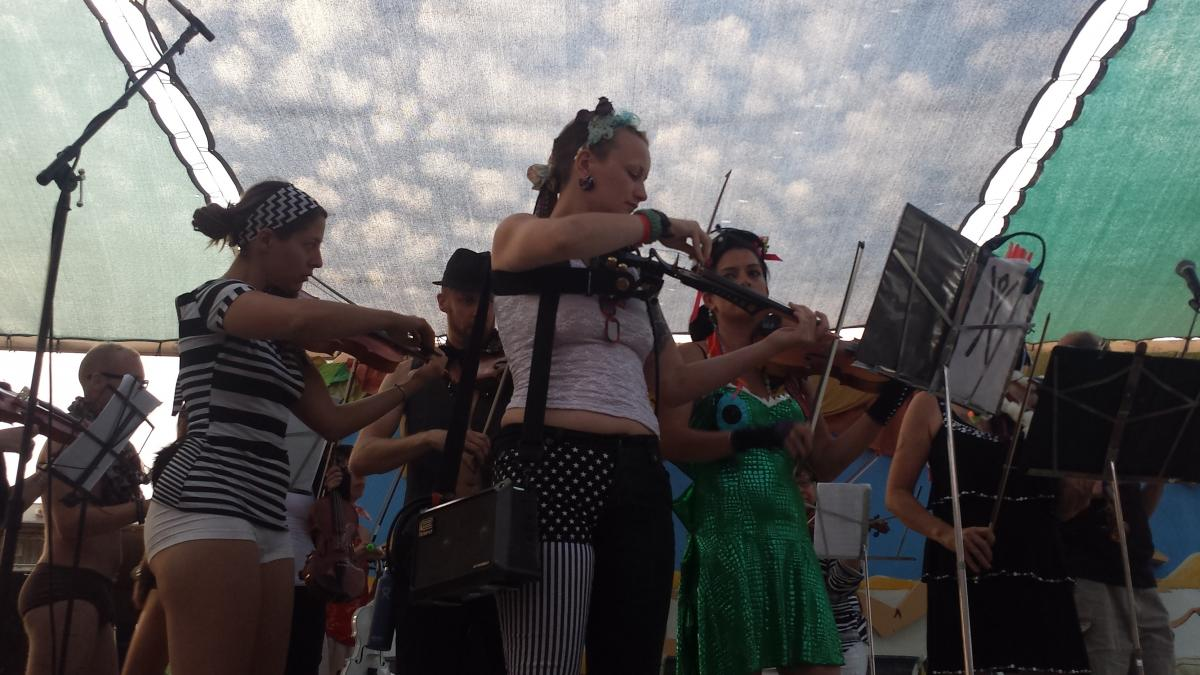 First-chair violinist Madelaine Ripley and other musicians in the Playa Pops Symphony warm up before a 2014 performance.