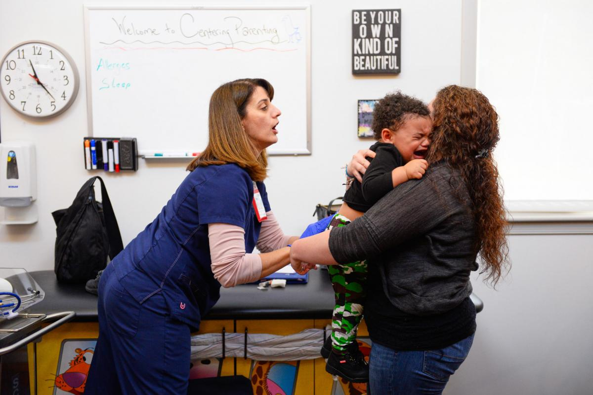 """Kelly (right) comforts her son after his hepatitis vaccination at the Children's Health Center in Reading, Pa. The baby's birth motivated her to do whatever it took to avoid relapsing into addiction, she says. """"I was in love with him."""""""