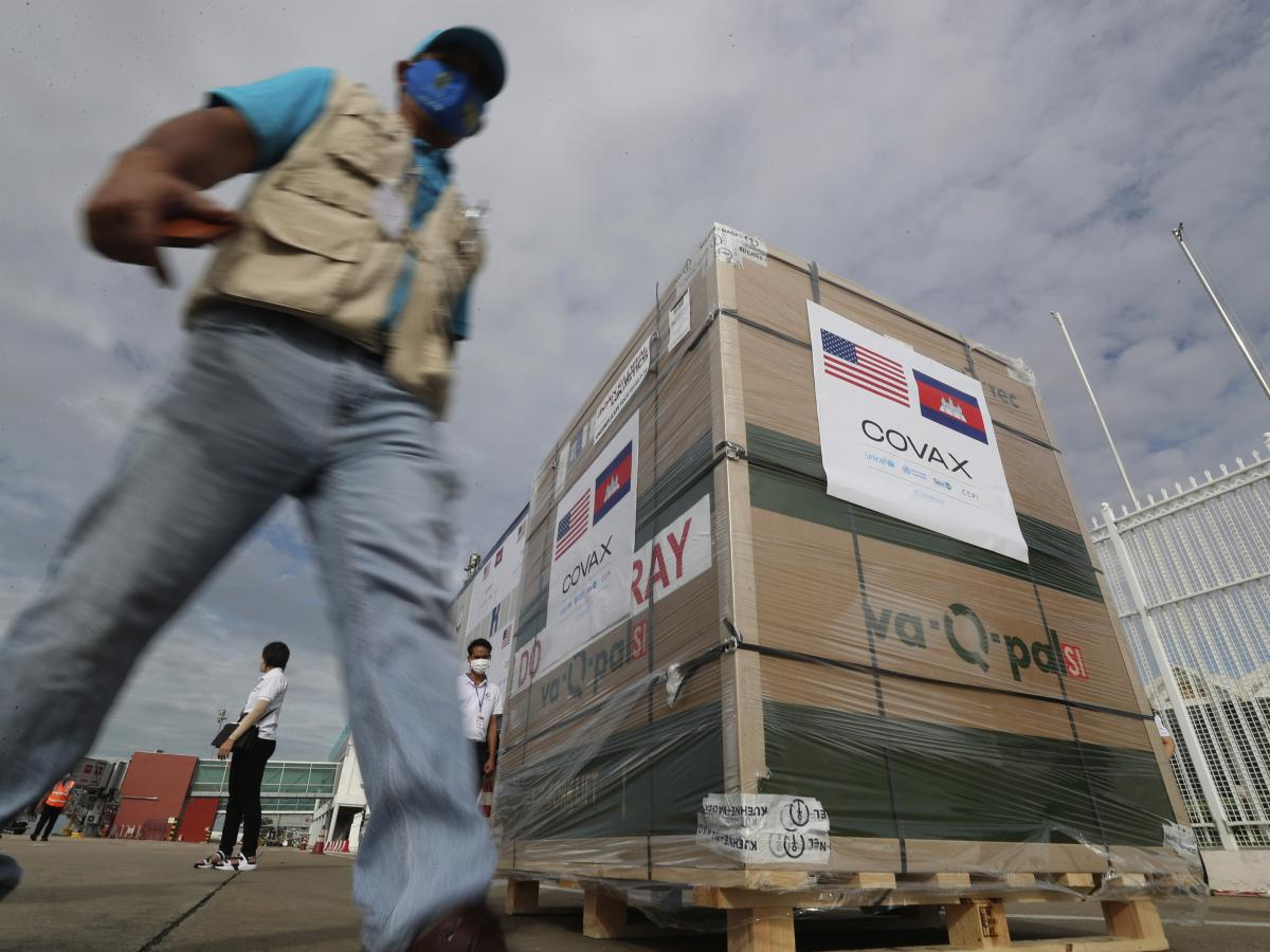 A man passes donated Johnson & Johnson vaccines after their arrival Friday at the Phnom Penh International Airport in Cambodia — the first batch of 1 million shots.