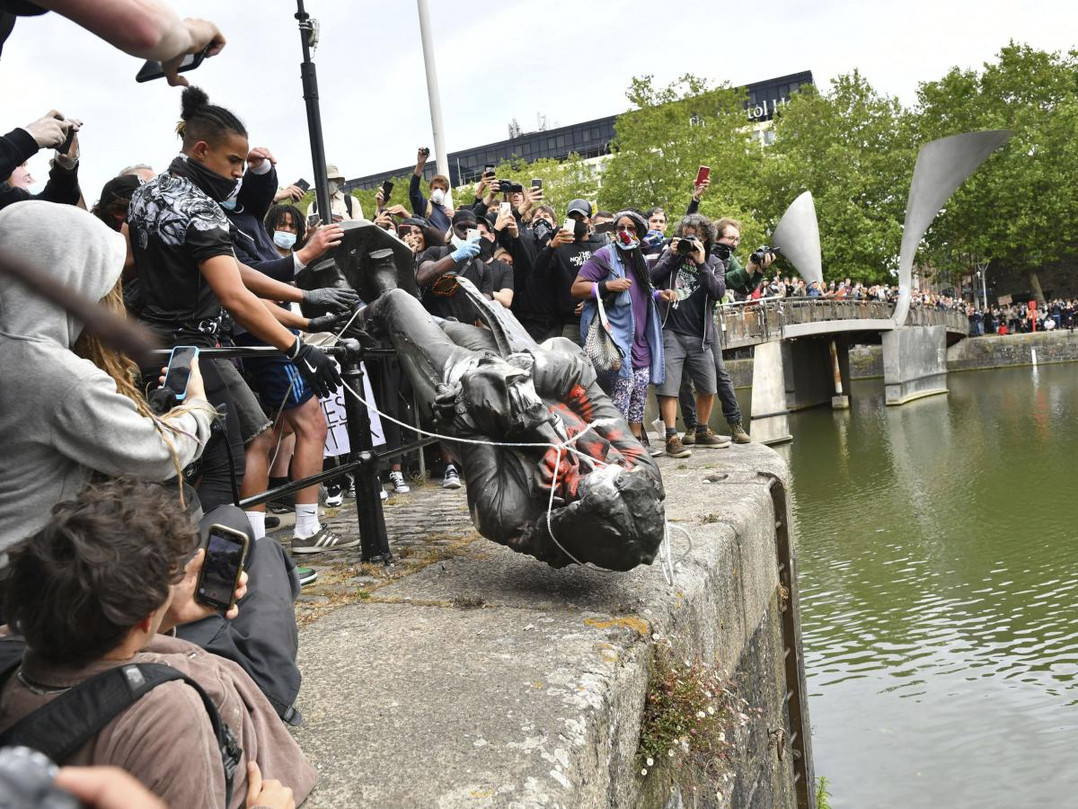 Protesters toss the toppled statue of Edward Colston into the harbor last month in Bristol. The monument to the philanthropist and slave trader had become a flashpoint of protests for racial justice in the U.K.