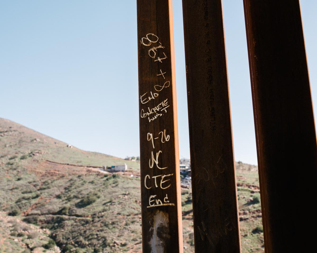 Construction notations written on the last steel slat in a section of the border fence.