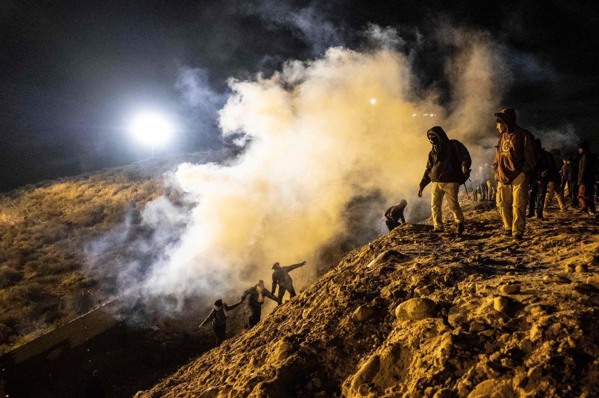 Central American migrants run away from tear gas thrown by the U.S. Border Patrol, after they tried to cross from Tijuana to San Diego on Jan. 1.