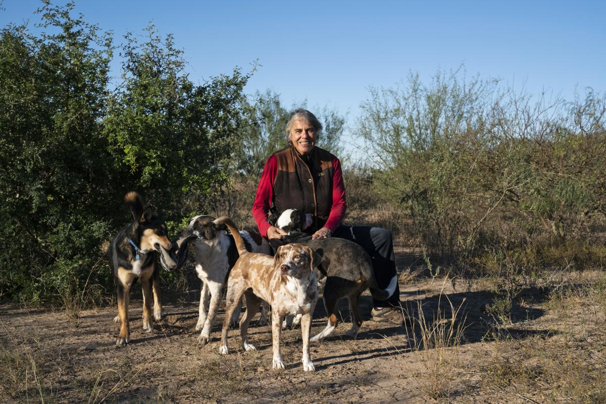 Betty Perez poses with her dogs in an area on her ranch that she is designating as a wildlife corridor. She is past president of the Friends of the Wildlife Corridor, which is adamantly opposed to the border wall.