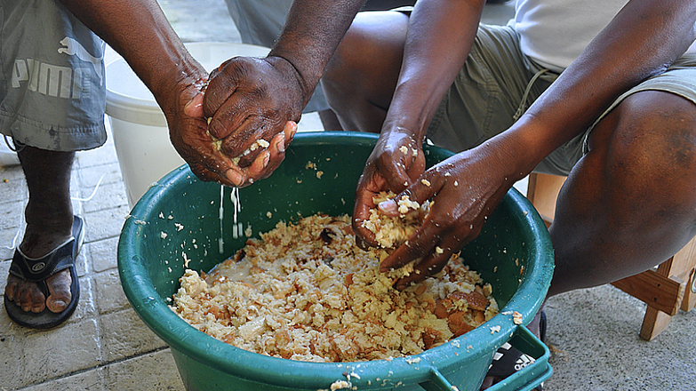 Pascal Maxo and one of his friends dig into a bucket of bread that has been softened in water. The bread is used in both kinds of boudin made by Maxo.