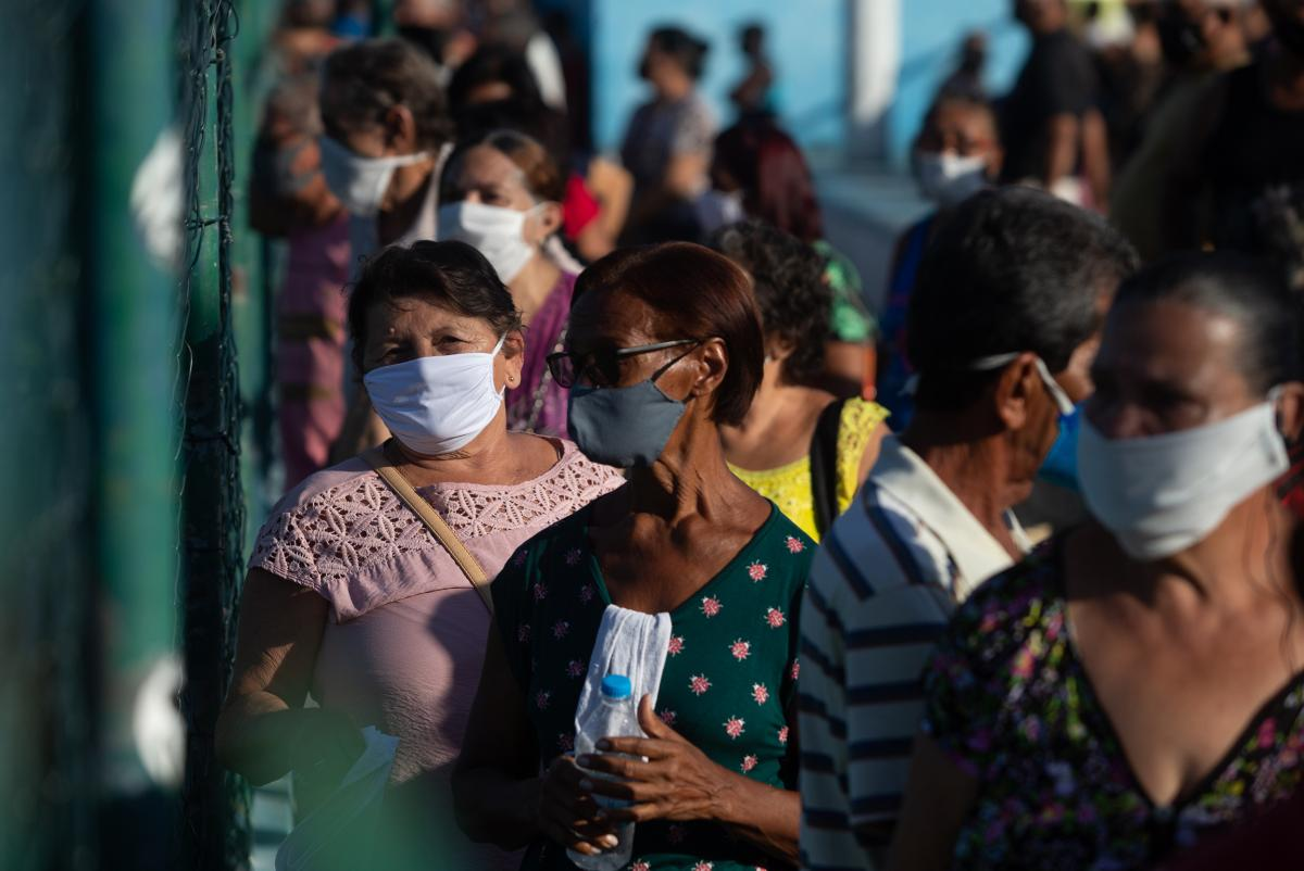 People line up for their COVID-19 vaccination in Duque de Caxias on March 22. After declaring he would never have the injection, Brazilian President Jair Bolsonaro now touts his health ministry's vaccination efforts and claims Brazil will acquire 500 mill