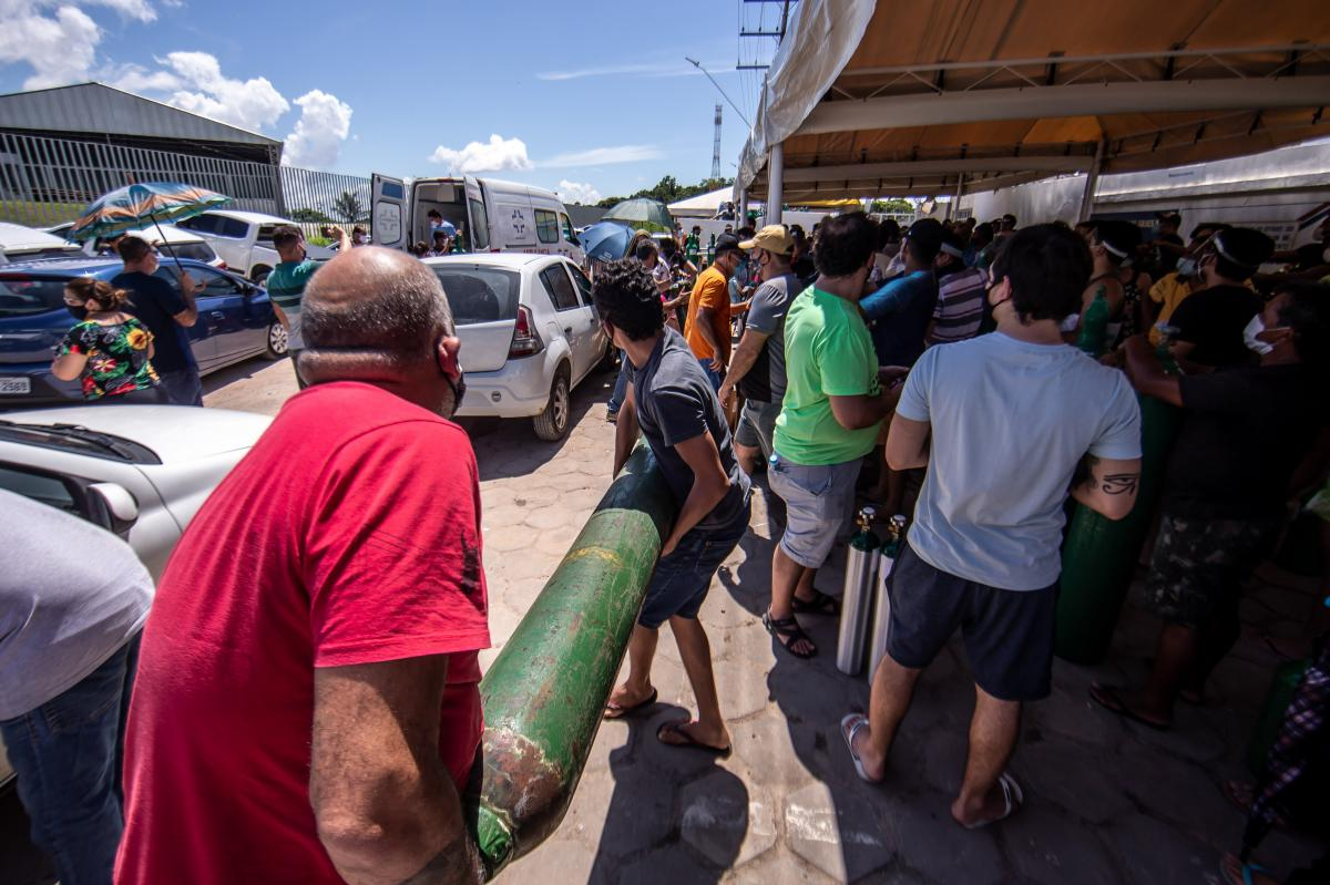 People wearing protective masks wait in line to refill oxygen bottles in January in Manaus, Brazil.
