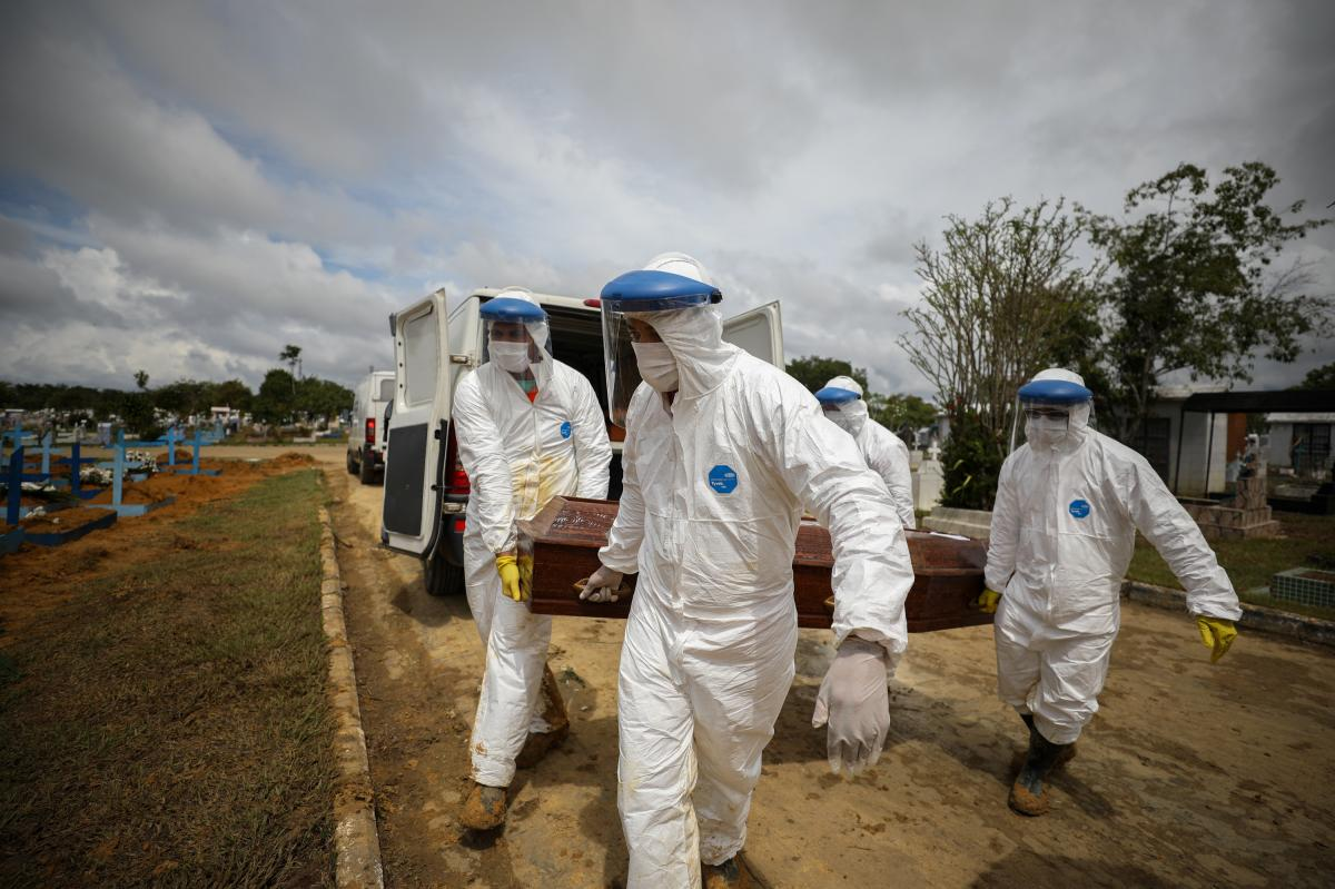 Workers in protective suits carry the coffin of a person who died of COVID-19 for burial at a cemetery in Manaus. In this Amazonian city alone, 4,430 people died within the first two months of the year.