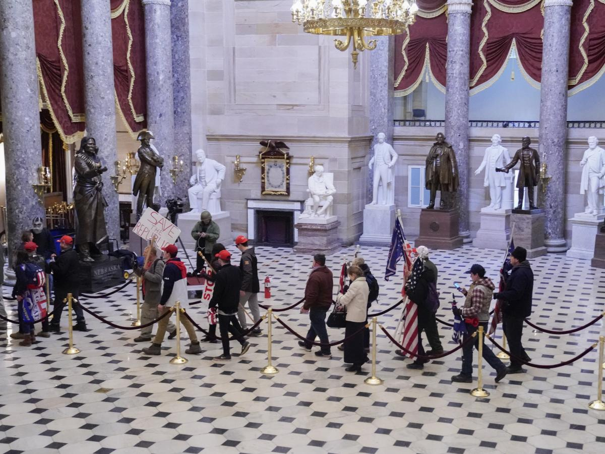 """Supporters of U.S. President Donald Trump walk through Statuary Hall of the U.S. Capitol on Jan. 6, 2021. A New York man was arrested on Thursday after allegedly boasting on a dating app that he had stormed the Capitol and """"made it all the way to Statuary"""