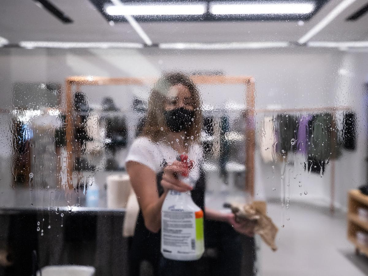 An employee wearing a protective mask cleans a plexiglass barrier before reopening at a Bloomingdale's store in New York City on Monday, June 22, 2020.
