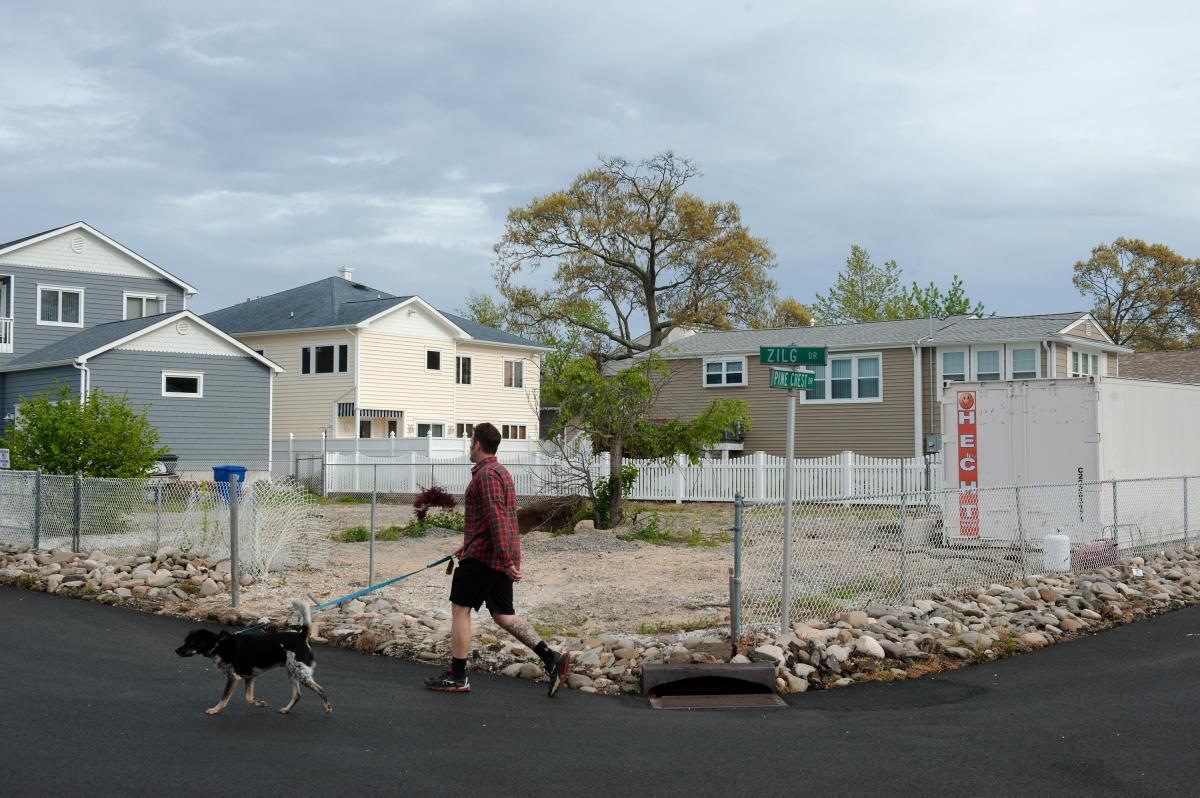 Life in the neighborhood continues on around the empty lot where Doug Quinn's house used to stand in Toms River, N.J.
