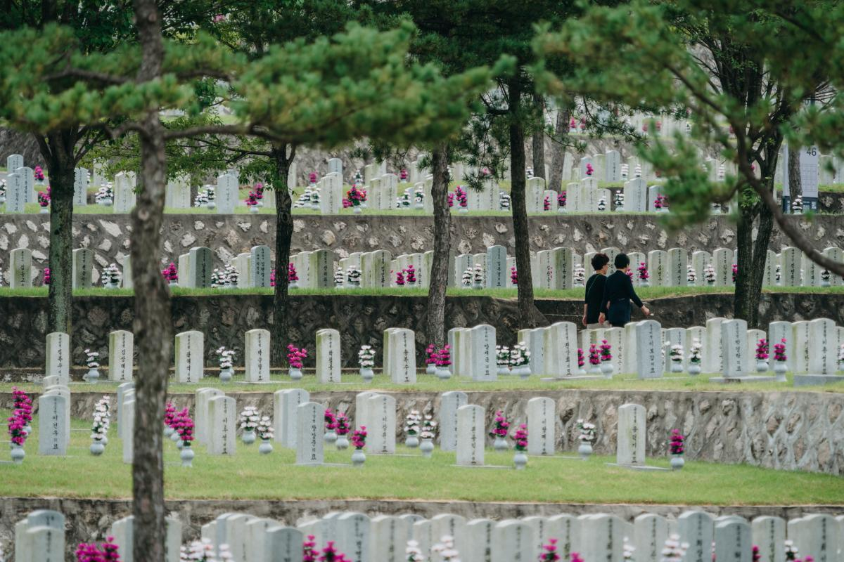 Visitors walk across a graveyard at the Seoul National Cemetery last week.