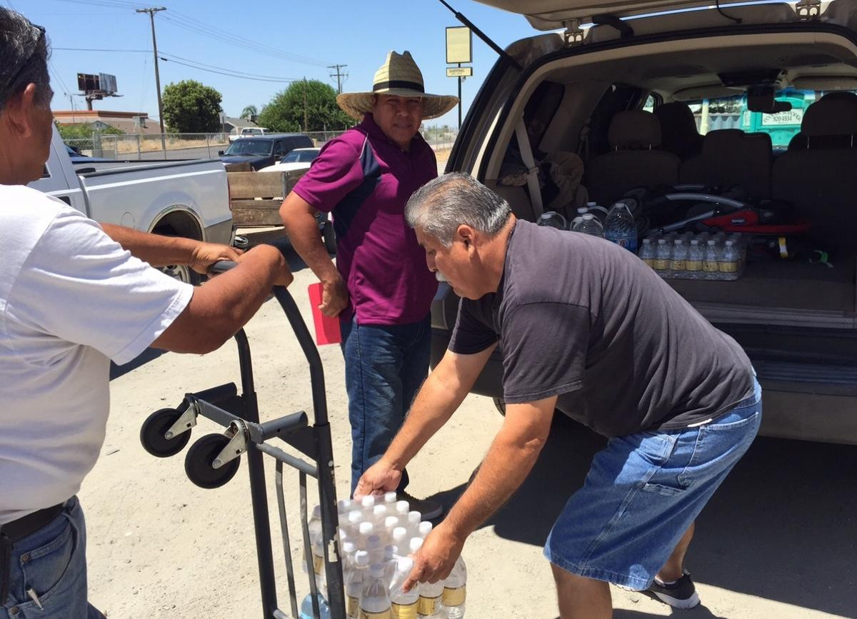 Pastor Frank Olmedo of the Spanish Church of the Nazarene in Porterville Calif., loads cases of bottled water into Humberto Hernandez's Suburban. These aid stations are a lifeline here, where residents like Hernandez have been living without water for mor
