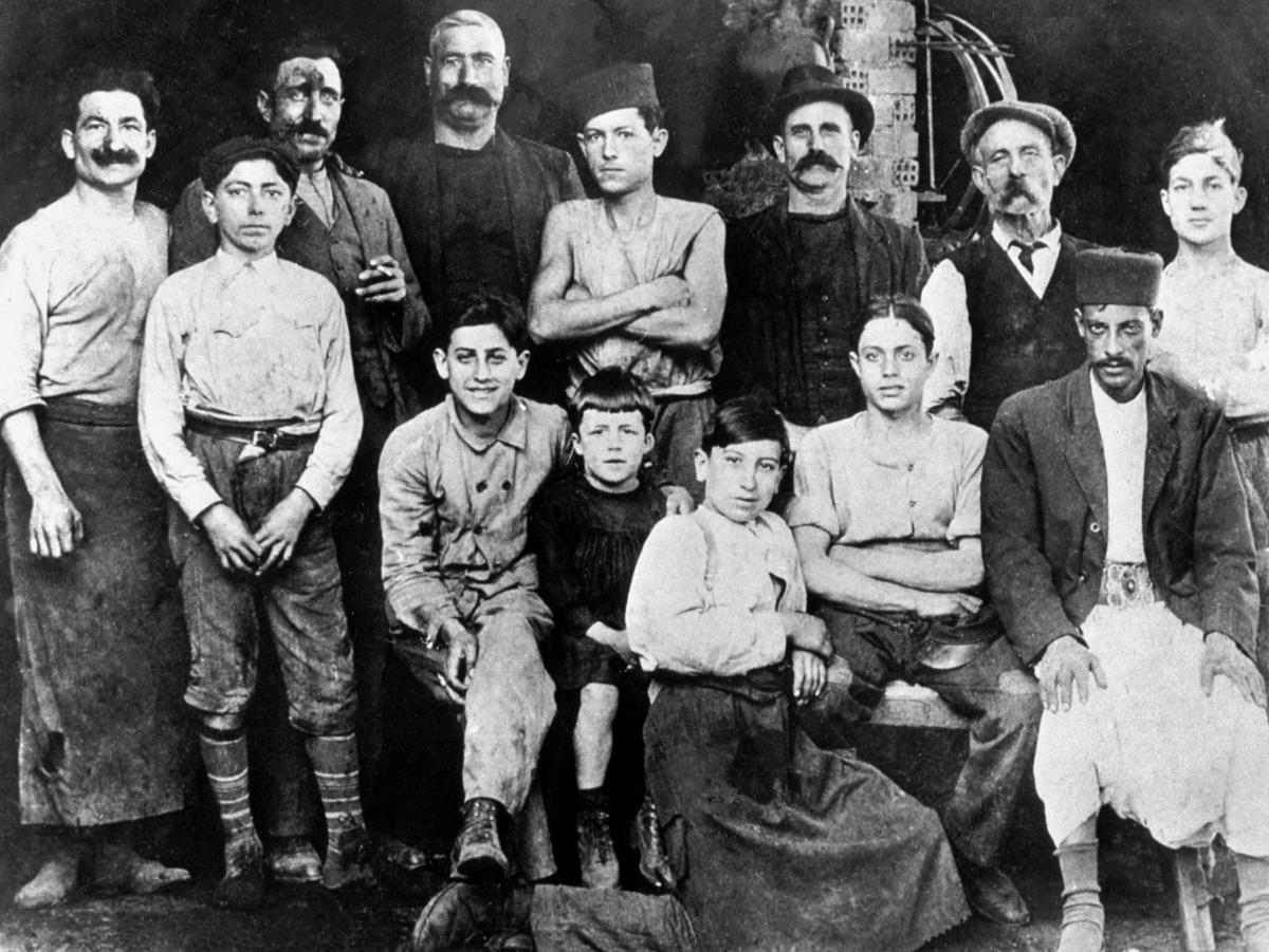 This photo from 1920 shows 7-year-old Albert Camus (center, wearing black suit) in the workshop of his Uncle Etienne in Algiers.