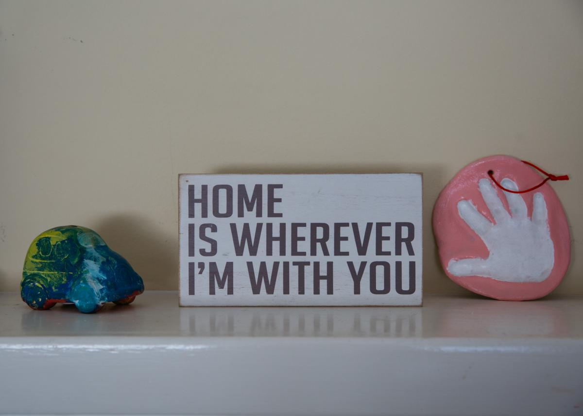 """Jeannine placed her children's school art projects next to a small board with the quote """"Home is wherever I'm with you"""" as a reminder that her current home is different from the home she grew up in."""