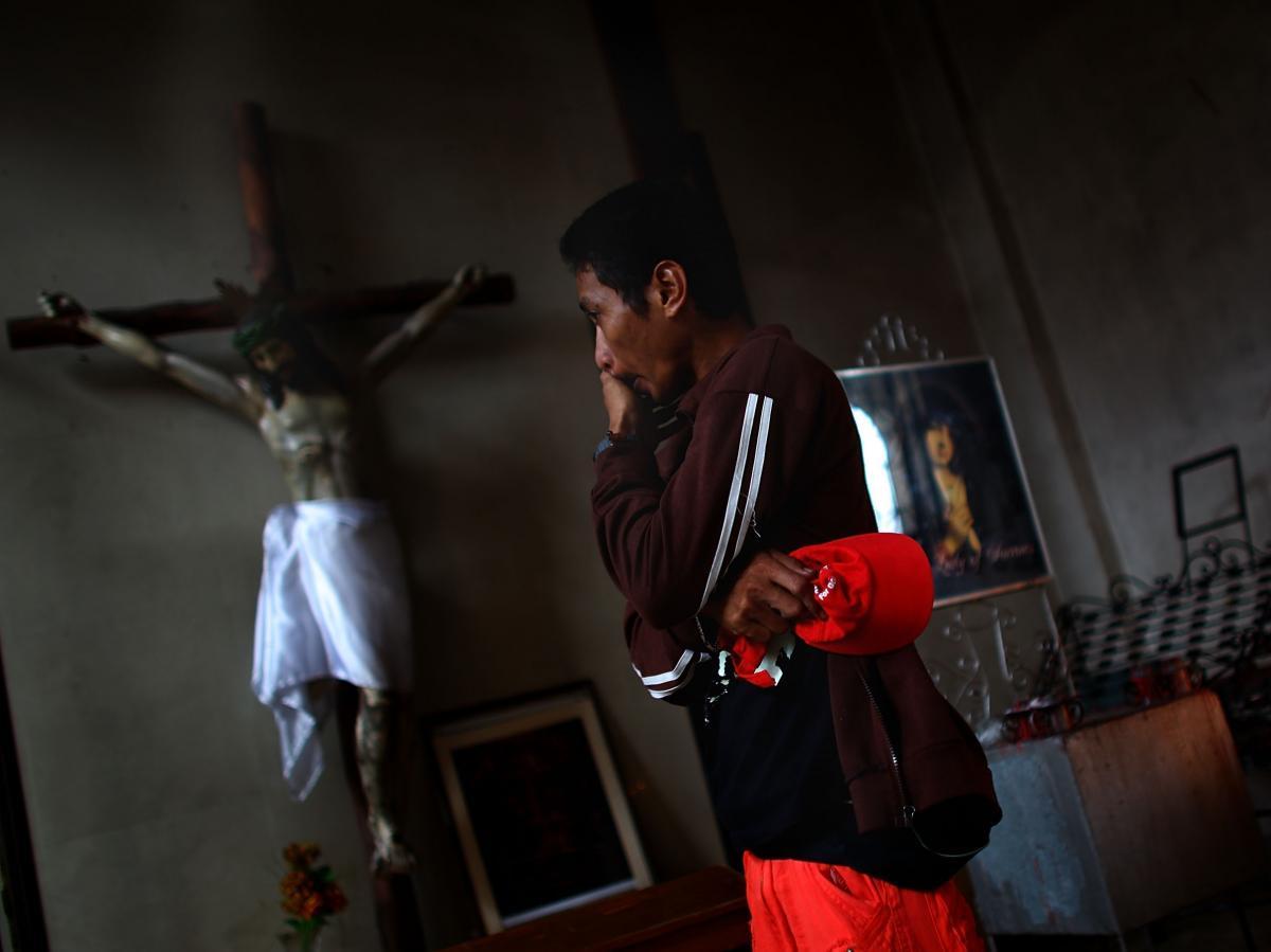 A Filipino man wipes the tears from his eyes on Sunday before morning Mass at Santo Nino church.