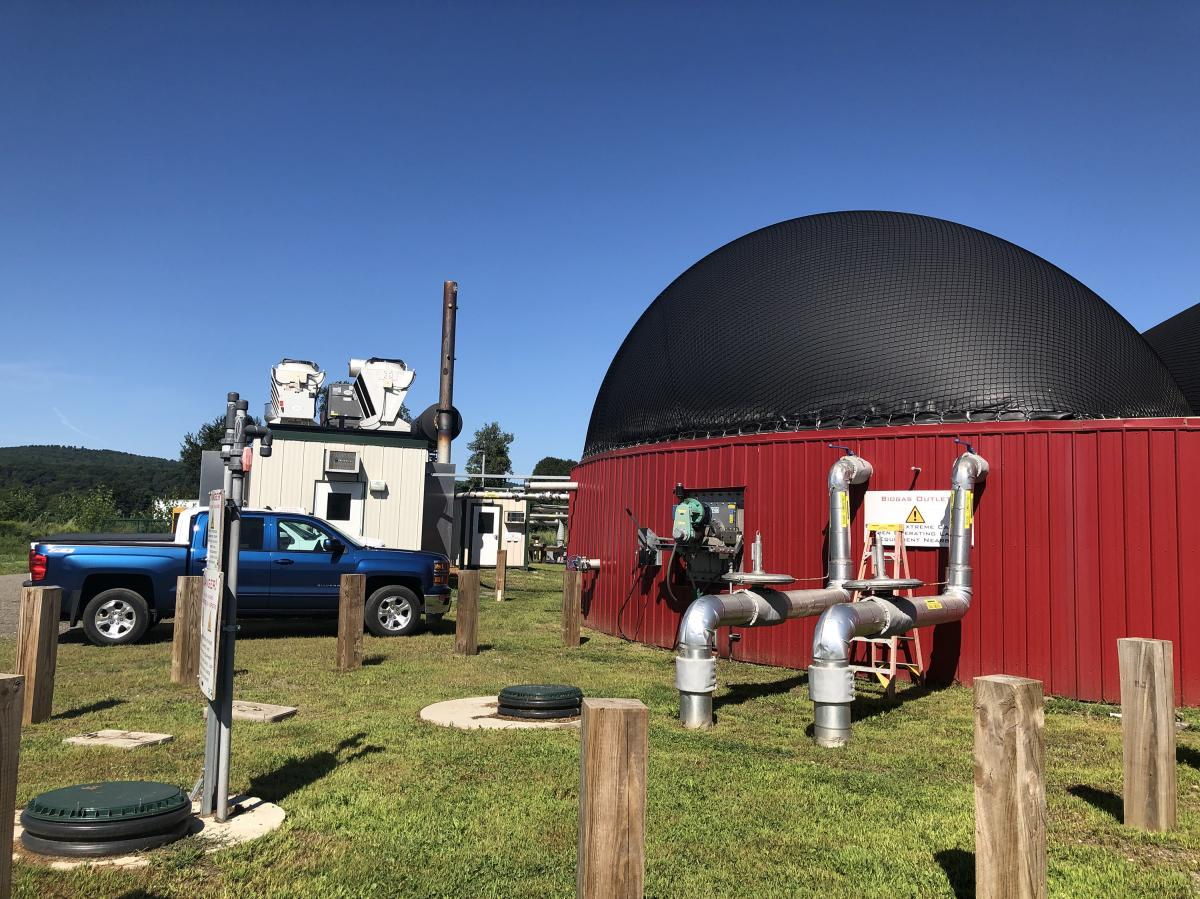 In the digester on his farm, Melnik combines food waste from Whole Foods and other local sources with manure from his cows. The mixture cooks at about 105 degrees Fahrenheit. As the methane is released, it rises to the top of a large red tank with a black