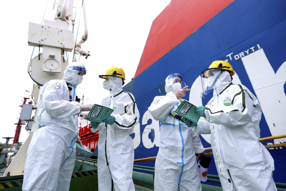 Police officers (left and second from right) wear protective gear as they explain how to fight the spread of Covid-19 to workers at Nanjing port in China's eastern Jiangsu province on August 4.