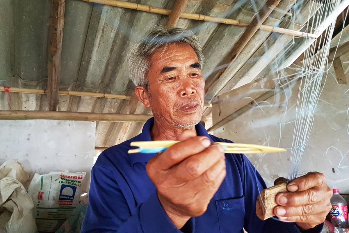 Fisherman Singhkha Wantanam repairs his net in his shack on the Mekong near Sob Ruak, Thailand. He complains China's upstream dams have caused drastic changes in water levels and a reduction in the number of fish in the river.