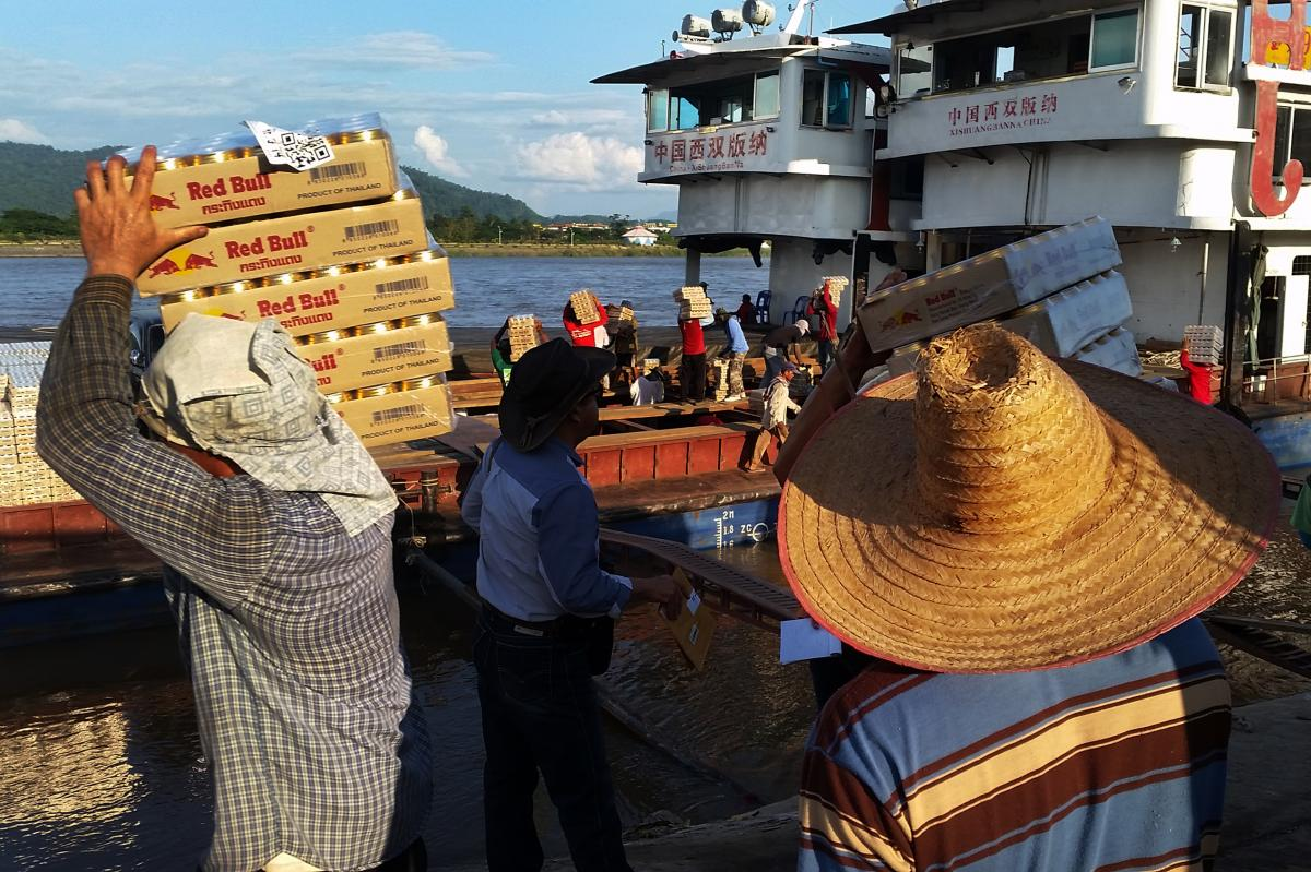 Day laborers outside Sob Ruak, Thailand, load energy drinks onto Chinese cargo boats on the Mekong for a trip upriver.