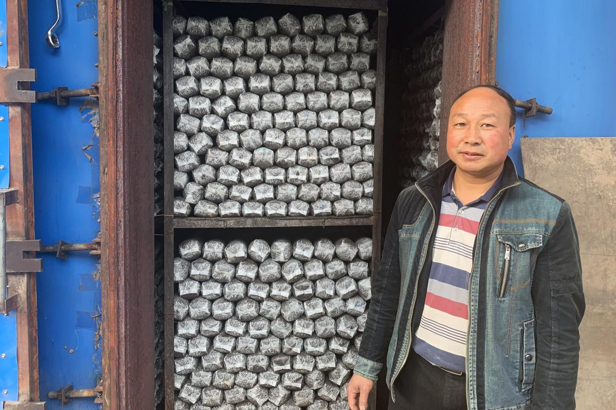 Sun Dahui, a mushroom co-op manager, stands outside a self-made oven, which heats logs of mushroom-growing medium. The cooperative hopes to expand into making mushroom-based sauces soon.