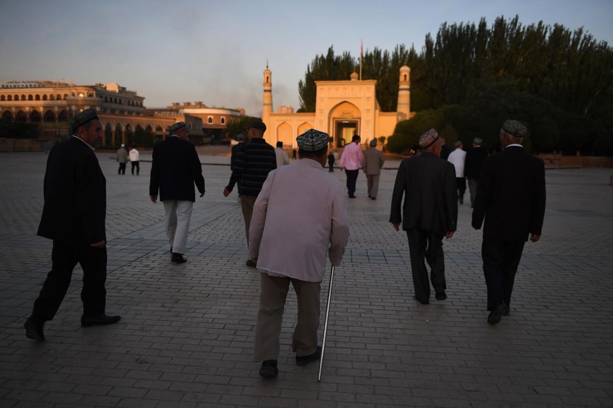 Uighur men walk towards the Id Kah mosque to attend prayers marking the end of Ramadan, in Kashgar in China's northwest Xinjiang region, in 2019.