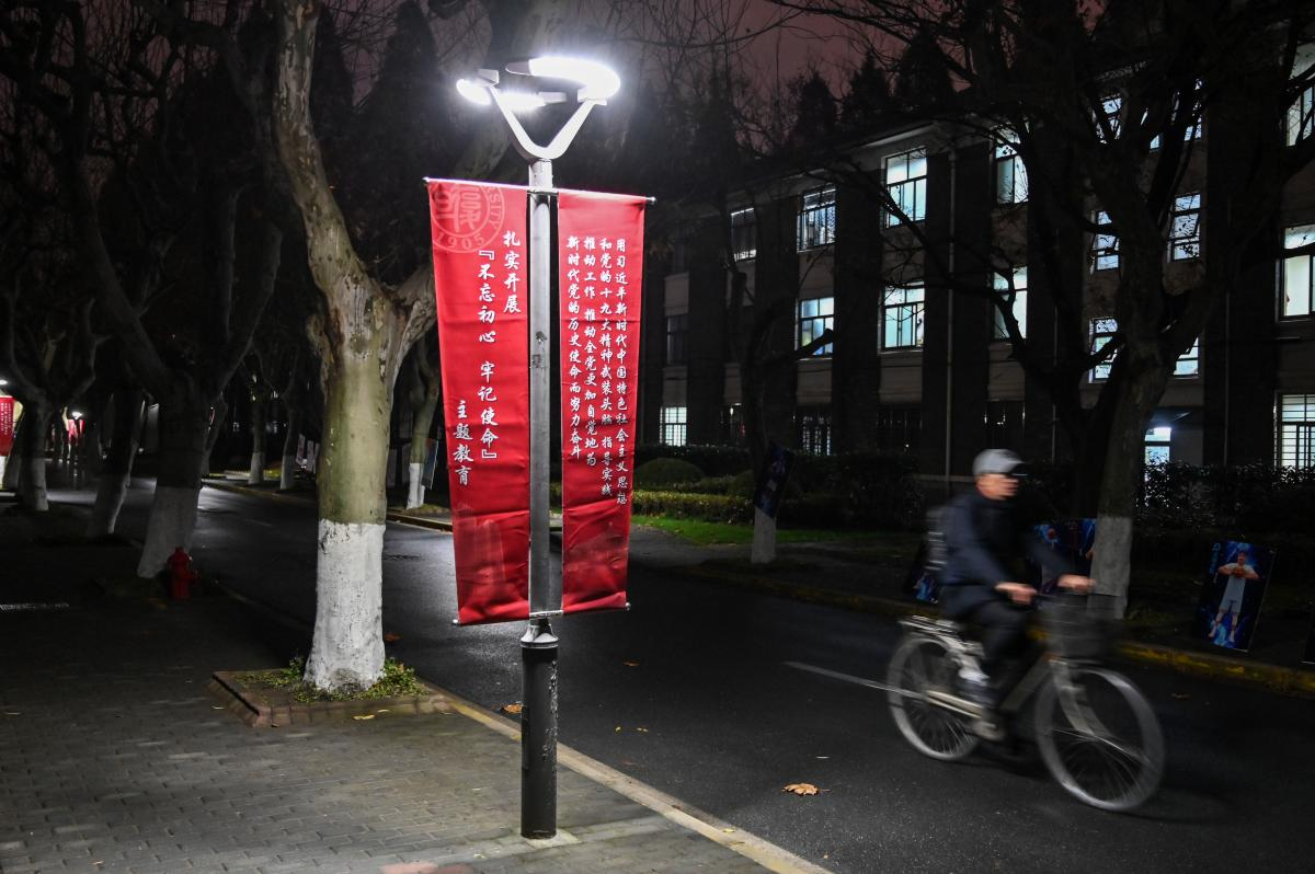 """A banner calls for institutions to adhere to the political philosophy of Chinese President Xi Jinping on the campus of Fudan University in Shanghai. When the university removed references to """"freedom of thought"""" from its charter, it triggered a rare act o"""