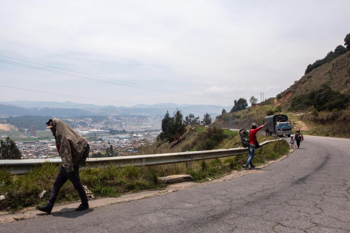 Caminantes walk back toward Venezuela on the road between Bogotá and Socorro, Colombia. Thousands cross the border each day. Many head back to their home country after failing to find work or shelter.