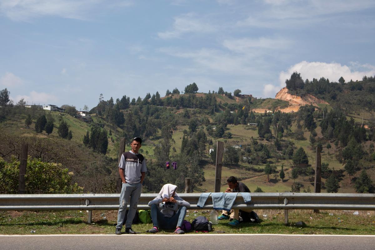 José Escobar (from left), Miguel Ángel Cordero and Jesús Escobar stop next to the road by a Red Cross aid station outside Pamplona, Colombia. The group came from Yaracuy, Venezuela, and had been walking for six days.