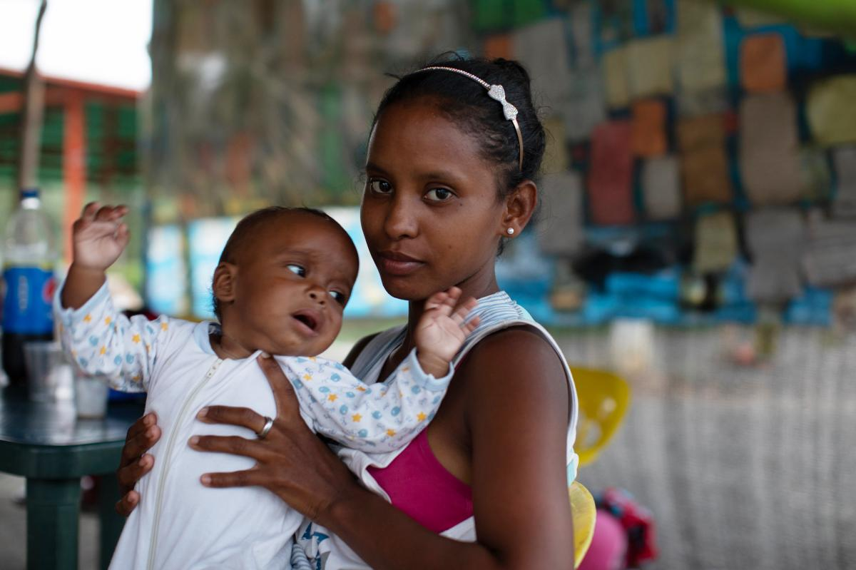 Yamibel Mendez, 22, holds her young child. They stopped at a roadside stand on the outskirts of Pamplona.