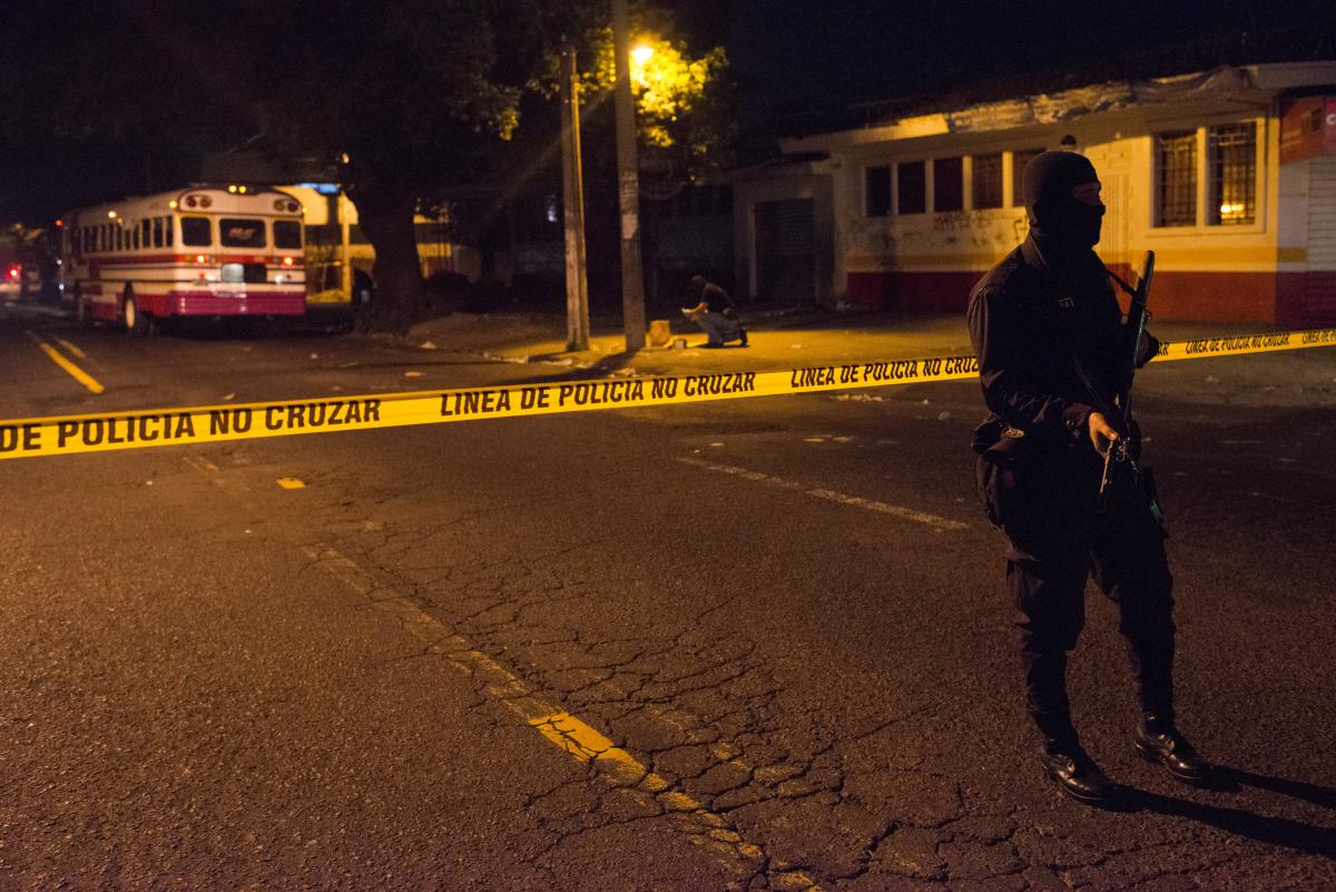 A policeman secures the scene of a homicide — the first in a string of bus driver slayings in El Salvador.