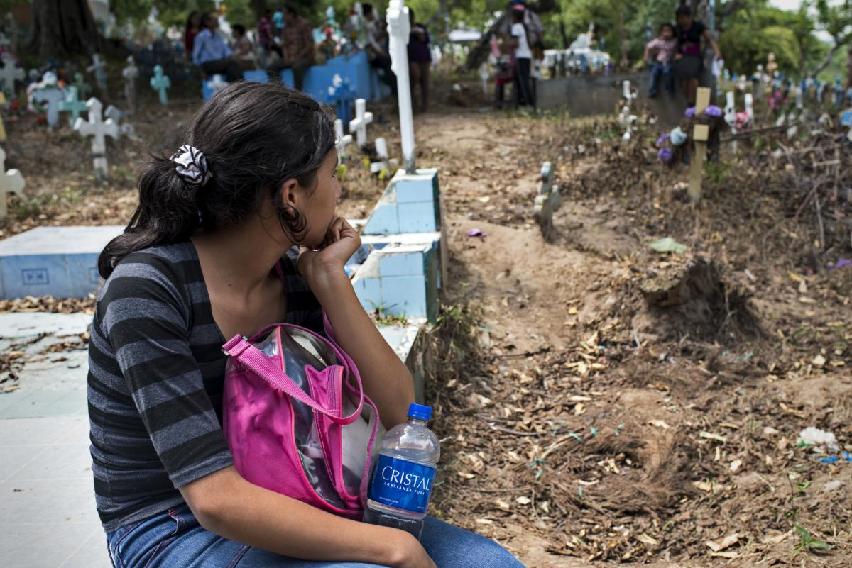 A girl observes her father's funeral at a local cemetery. Her father was one of the bus drivers killed during the ban imposed by gangs in San Salvador.