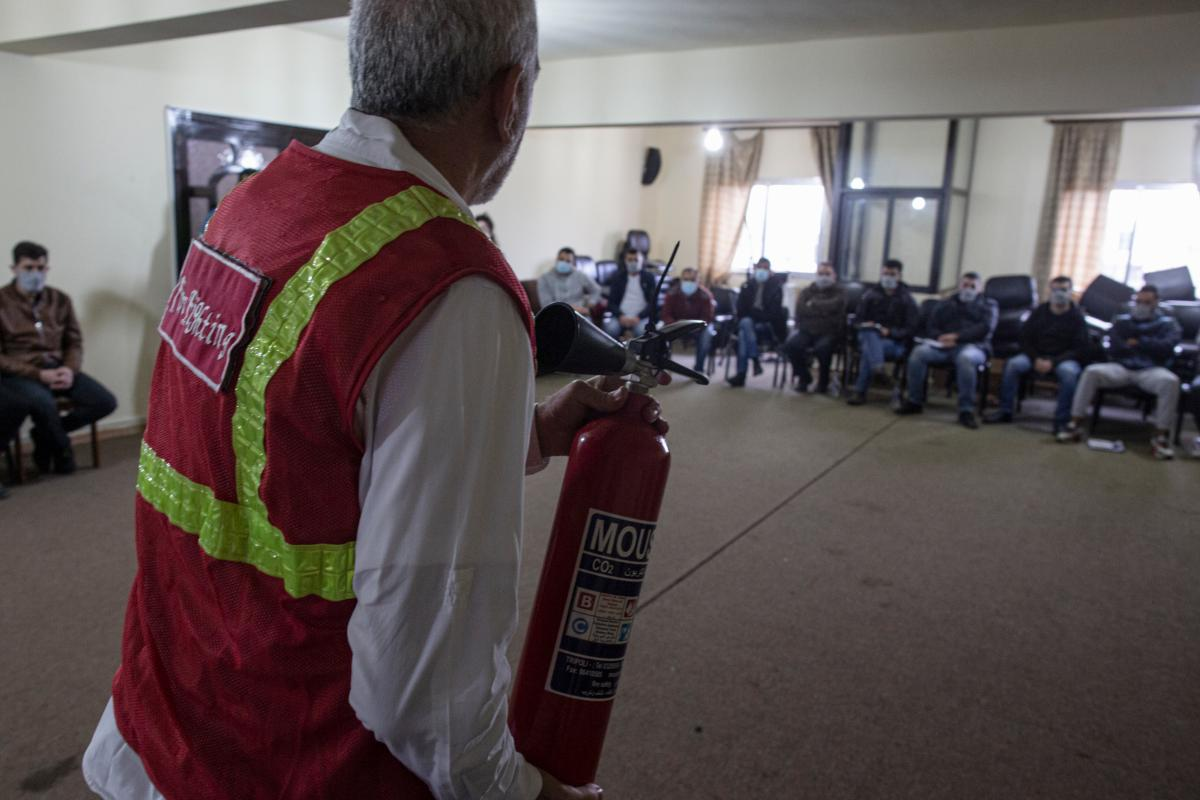 Ali Moussa, 60, teaches a fire-fighting course to a room full of volunteers in the town of Mishmish.