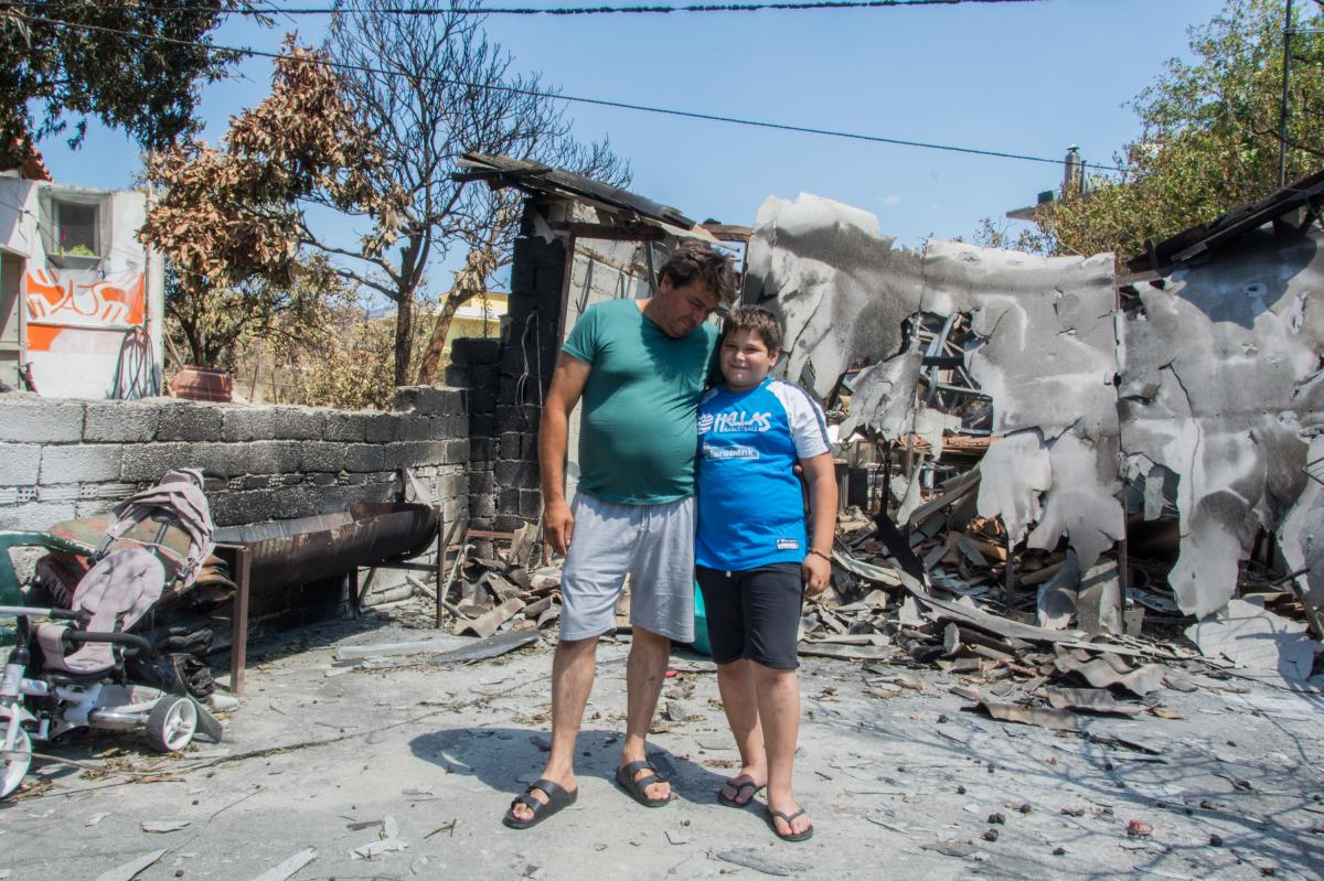 """Stathis Steffos hugs his 11-year-old son, Kostas, outside their burned home in the village of Rovies. Kostas used a makeshift broom to help his father beat back flames as they rescued the family sheep. """"But he cried when he saw what was happening to us,"""""""