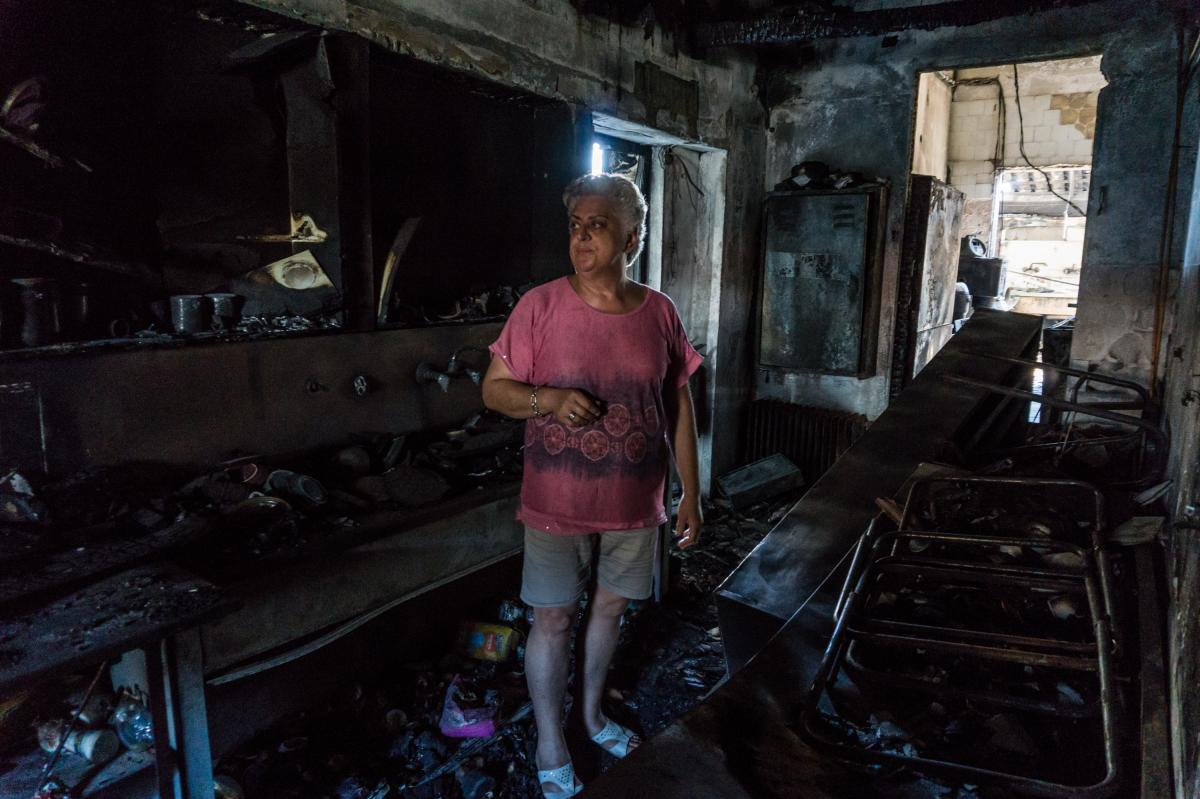 """Zoe Chalasti examines the remains of Noufaro (Water Lily), the pastry shop in the village of Rovies in northern Evia that she owned with her husband for 38 years. The recent fires destroyed it, and she will not rebuild. """"We can't afford it,"""" she says."""