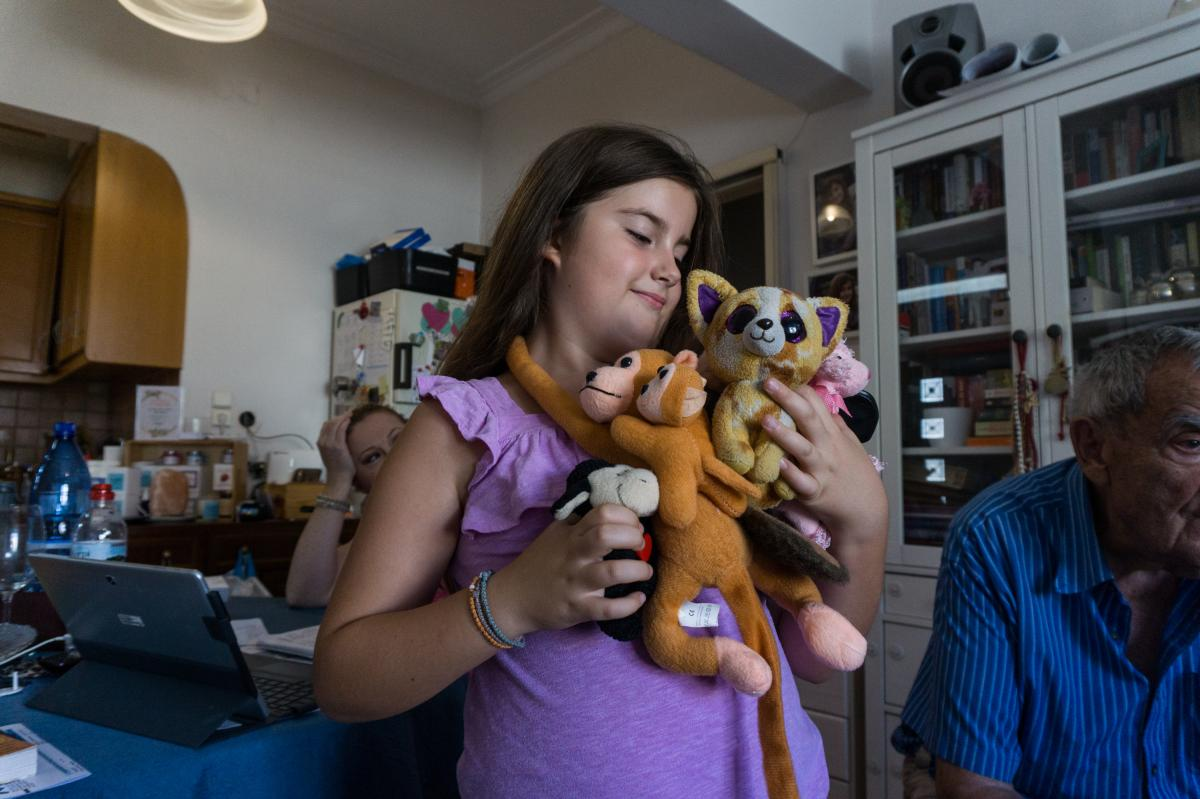 Konstantina Tsamouras, 9, holds her favorite stuffed animals at her home in the village of Limni in northern Evia. Now that the forest where she used to play has burned, she worries that it will be even hotter in the village. The heat already makes her fe