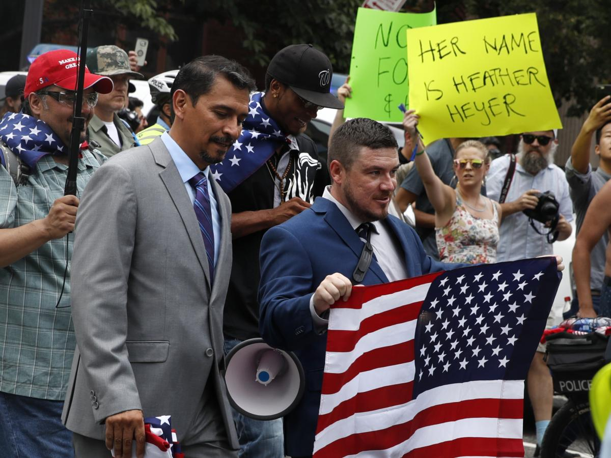 Far-right extremist Jason Kessler (center) walks to the White House in 2018 on the first anniversary of the Unite the Right rally. In the background, a protester holds a sign invoking the name of Heather Heyer, the woman killed in the 2017 rally in Charlo