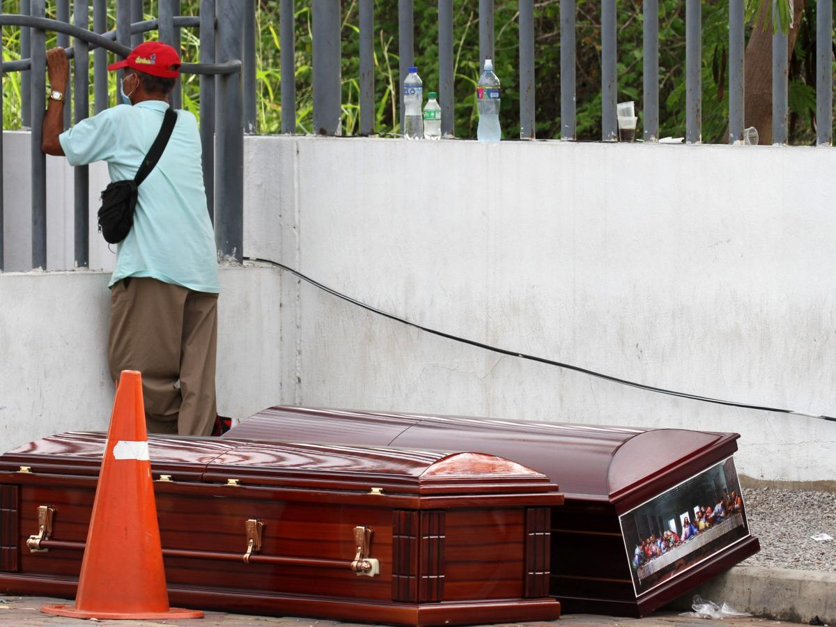 A man wearing a face mask waits for the corpse of a relative outside a hospital in Guayaquil, Ecuador. Ecuadorians express outrage over the way the government has responded to the number of deaths from COVID-19. Many suspect there are more deaths than the