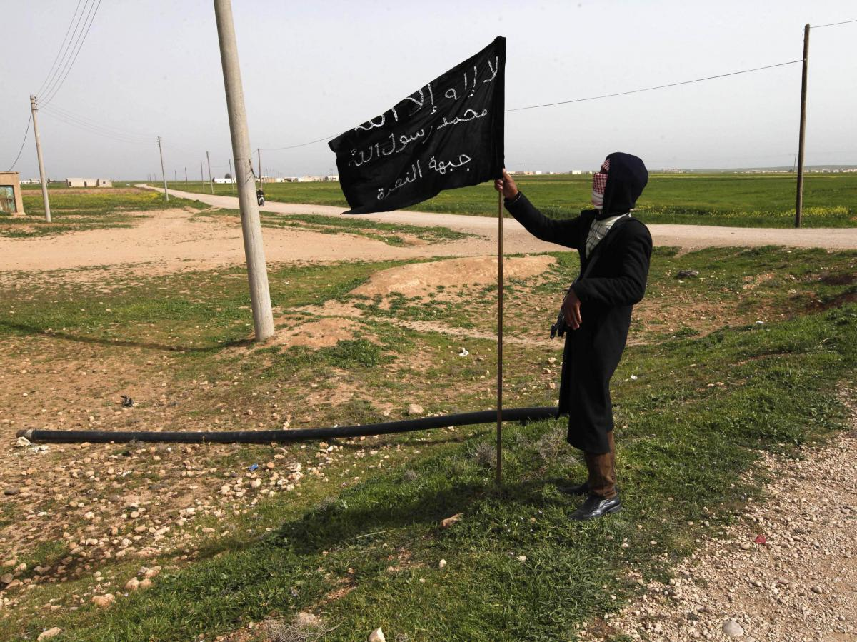 A member of an Islamist group holds a flag in Raqqa province, eastern Syria, on Tuesday. Recently, militants there posted leaflets announcing that anyone who supports democracy is an infidel — a serious offense under Shariah law.
