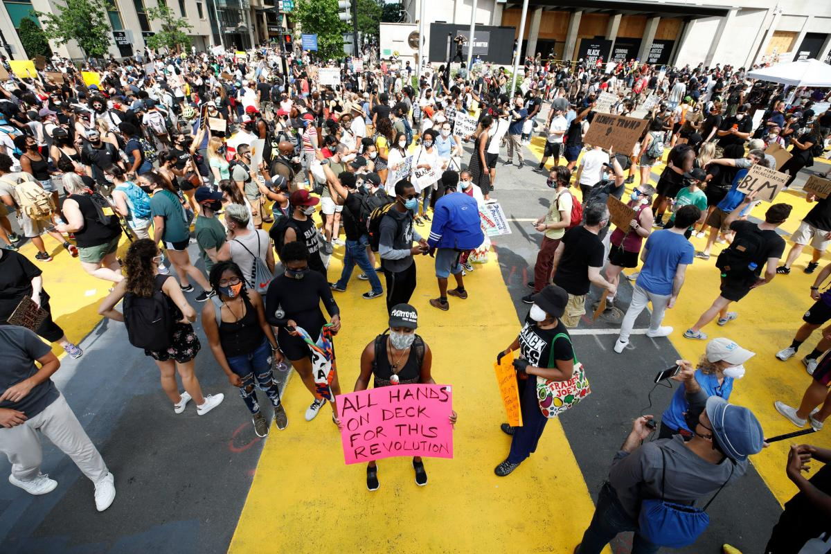 "Protestors walk over a mural that reads ""BLACK LIVES MATTER"" in yellow capital letters down a two-block stretch of 16th street that Mayor Muriel Bowser officially renamed Black Lives Matter Plaza."