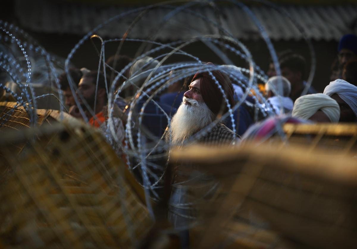 An Indian farmer looks through barbed wire that police put up at a protest site Thursday at the Delhi-Haryana state border.