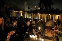People gather on Monday at Lake Merritt in Oakland, Calif., for a vigil honoring the victims of the Friday night fire at the Ghost Ship warehouse, where 36 people were killed.