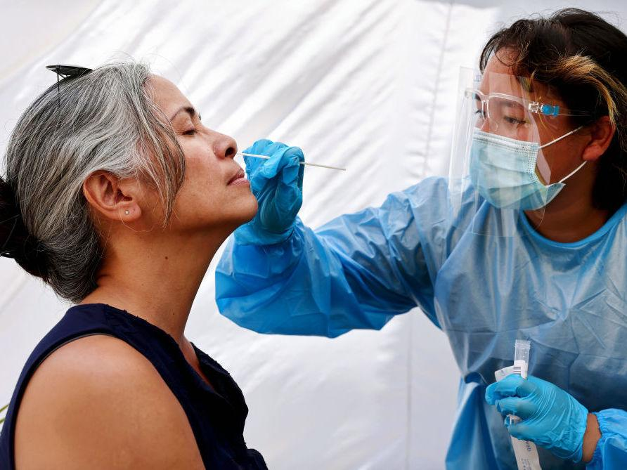 A medical assistant administers a COVID-19 test to a person at Sameday Testing this week in Los Angeles.