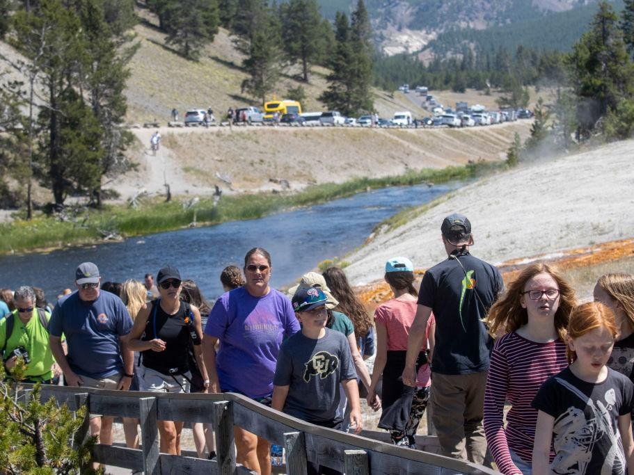 Tourists crowd in to the Midway Geyser Basin on July 14, at Yellowstone National Park in Wyoming. Yellowstone is one of many national parks seeing record numbers of visitors this summer, even as coronavirus cases are rising in many states.