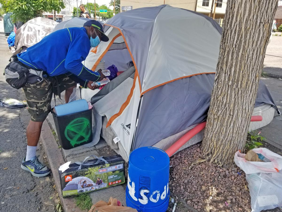 """David Scott loads supplies into his tent home in downtown Denver. """"As long as they keep it to where we're getting cleaned, not swept, it's all right,"""" says Scott."""