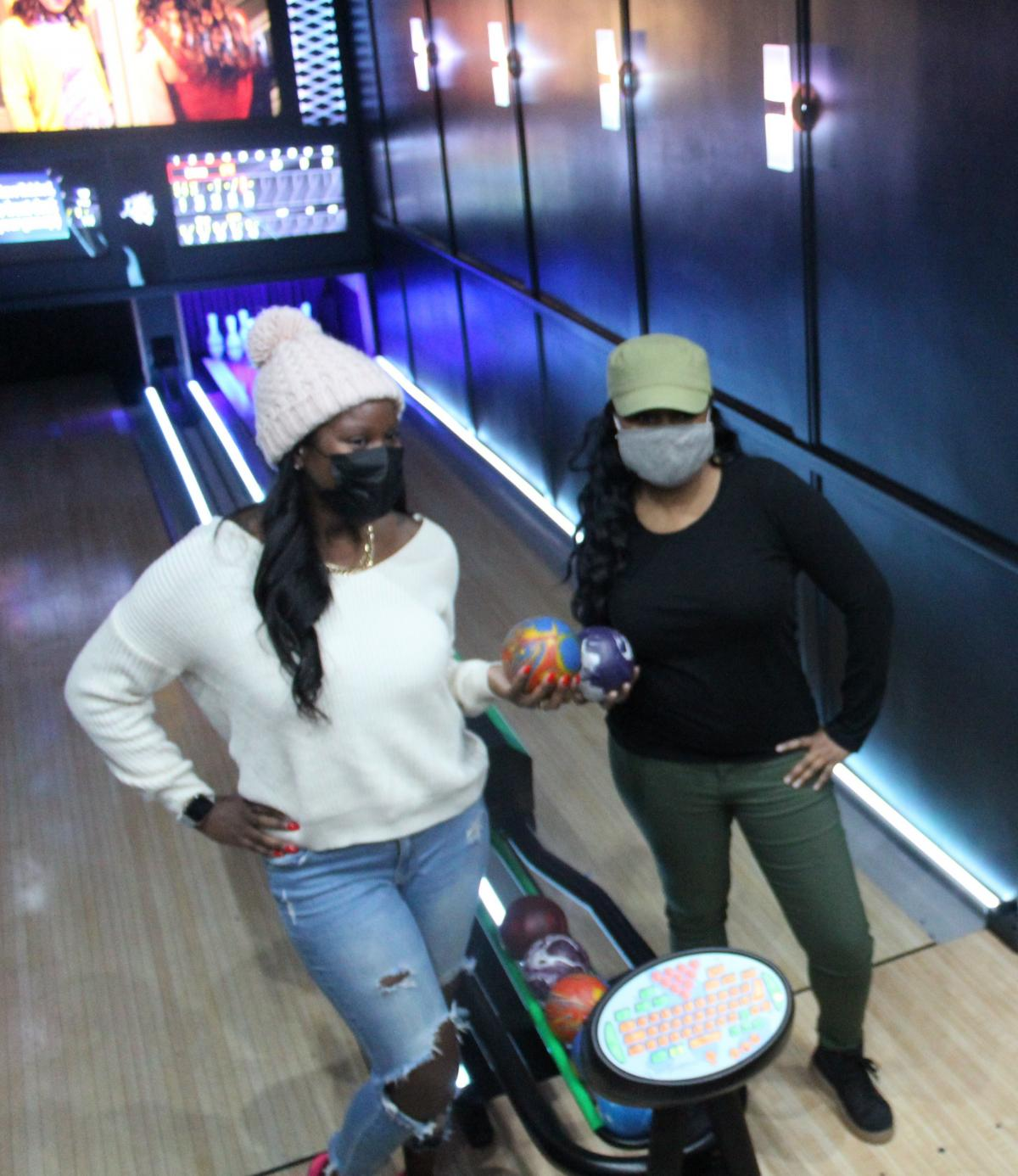 Sharise Crumley of Southfield, Mich., and Linnea Nelson of Oakpark, Mich., hold Lucky Strike's sized-down bowling balls. They weigh about 3 to 4 pounds and don't have any holes.